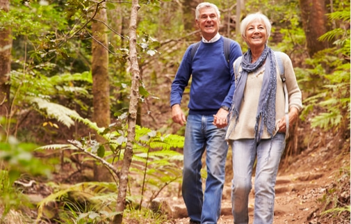 Mature couple holding hands and hiking in the woods.