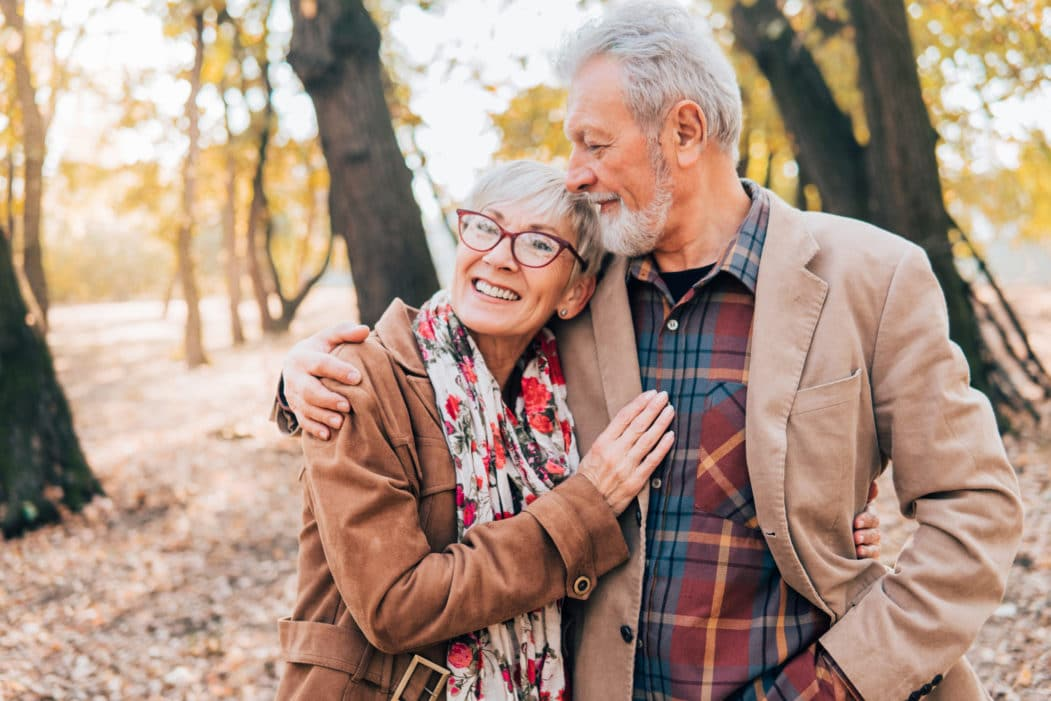 Senior couple holding each other while walking through park